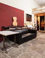 Living area in workshop with string instruments, rustic stone floor, black leather sofa and dark red accent wall panel