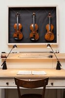 Three violins in display case above vintage table with drawers lit by tow modern desk lamps