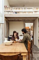 Young couple sitting at rustic wooden table on old, grey stone floor; view into workshop and of wooden mezzanine with bookcase balustrade