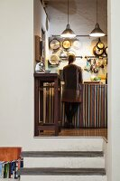 Raised, vintage kitchen with pans hung on wall and young woman standing at kitchen counter with striped curtain on base units