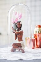 Figurine of Caribbean girl holding delicate summer flower under glass cover on white doily