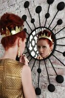 Festively dressed woman with crown in hair applying makeup in front of mirror