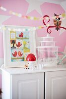 Framed comic page and birdcage on white cabinet against pink mural with stylised owl