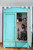 Vintage cupboard painted pastel turquoise with patinated surface; open door showing view of ornaments