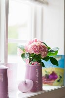 Pale pink hydrangeas in pale lilac jug on windowsill