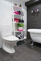 Bathroom with towels on ladder shelves, white clawfoot bathtub and charcoal tiles