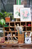 Workspace; containers in front of shelves of gardening utensils with vintage pictures of roses on top