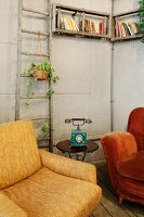 Vintage furnishings with antique telephone on small side table below rustic, wall-mounted book shelves