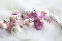 Pink Christmas tree baubles amongst feathers
