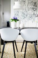 Retro, white shell chairs with black frames around table in front of black and white drawing on wall