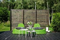 Green wicker easy chairs and set of white side tables on wooden deck in front of wooden screen
