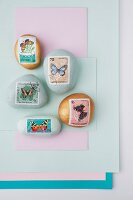 Paperweights made from painted pebbles decorated with butterfly postage stamps