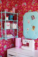 Corner of girl's bedroom with pink floral wallpaper, turquoise fabric pin board and matching wall-mounted shelves