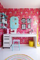 Modern, white desk and wallpaper with floral pattern on pink background in nostalgic, child's bedroom