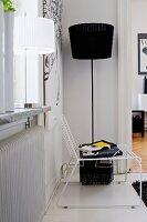 Delicate, white Spaghetti Chair in front of black standard lamp in corner