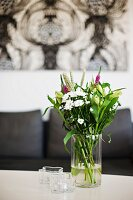 Garden flowers in glass vase and Alvar Aalto tealight holders on table with sofa below artwork in background