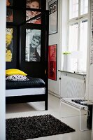 Detail of four-poster bed with black metal frame in front of posters on black wall in traditional interior