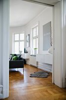 Period apartment with open double doors and animal-skin rug on parquet floor in interior with modern furniture