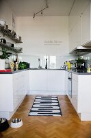 Black and white patterned rug on herringbone parquet floor in open-plan, white designer kitchen