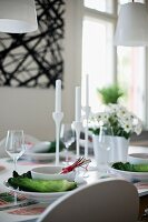 Place settings with white bowls on arrangements of cabbage leaves and white candlesticks on table