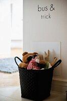 Black basket of soft toys on floor