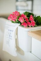 Bouquet of pink roses in white sink