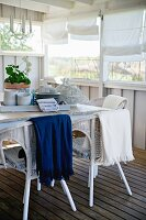 Tray of crockery on table, white wicker chairs on wooden floor of partially wood-clad veranda