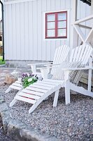 White wooden loungers on gravel terrace in front of wooden house with red window