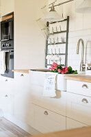 Detail of white, country-house kitchen with roses in sink and white metal bottle rack on wall