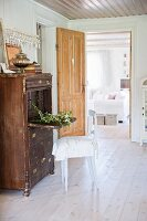 Rustic chair at vintage bureau in front of open door with view into living room
