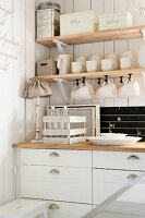 Kitchen counter with white base units below wooden shelves of storage containers and cups hanging from hooks