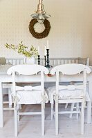 White-painted, wooden kitchen chairs with curved backrests at dining table in front of wicker wreath on wall