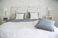 Double bed with white-painted wooden headboard, white blanket and grey and white pillows and scatter cushions