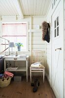 Bedside table below window and kitchen chair against white wooden wall in rustic bedroom