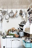 Pots and pans hanging from rod over cooker with kitchen utensils