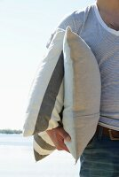 Man on beach holding two cushions
