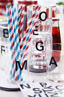 Drinking glasses with black alphabet stickers and drinking straws