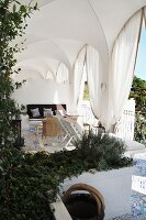 Seating area with loungers in cross-vaulted loggia with draped curtains and planted troughs