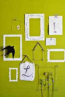 Stems of lavender in wire and paper picture frames on green wall