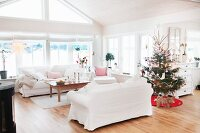 White sofa set and decorated Christmas tree in open-plan interior with rustic character