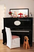 Straw figurine next to chair with white loose cover in front of black piano