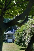 Round summer house with lattice windows in summer garden