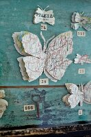 Butterflies hand-crafted from maps on weathered wall