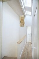 Narrow landing with wooden floor next to head of staircase and paper pendant lamp suspended from ceiling with skylights
