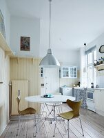 Dining area with classic-style shell chairs below retro, metal pendant lamp in rustic kitchen with cream wood panelling