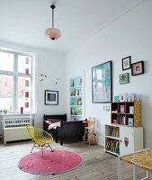 Retro easy chair with yellow cord seat and metal frame on round rug and wooden floor in child's bedroom