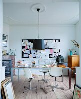 Retro swivel chairs with white shell seats at modern table below pendant lamp with black lampshade suspended from stucco ceiling; pinboard on wall in background