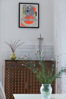 Vase of flowers on table in front of radiator with metal cover