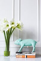 Pig figurine on stacked books and glass vase of flowers against of white, wood-panelled wall