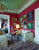 Sofa set with floral upholstery in corner of grand lounge with gilt-framed pictures on deep pink walls